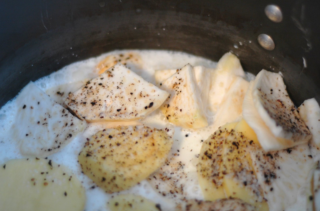 Simmering sliced celeriac and potatoes in milk and cream for Au Gratin